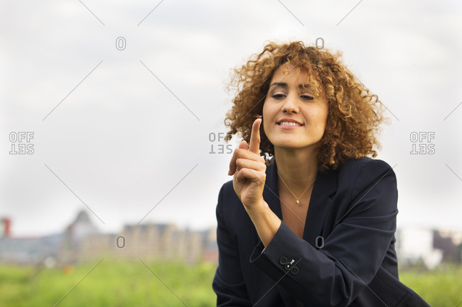 Smiling businesswoman with curly hair holding insect against cloudy sky in city