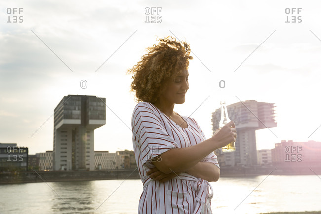 Mid adult woman holding beer bottle while standing against river and buildings in city