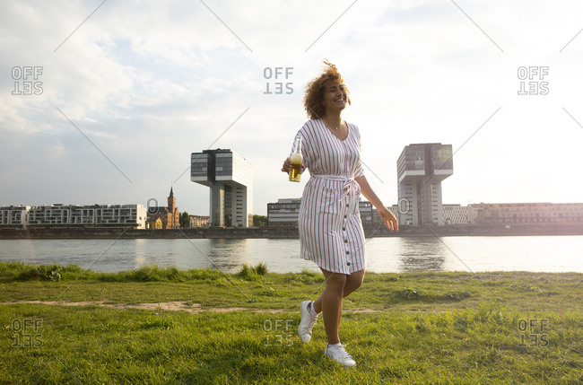Cheerful woman with beer bottle walking on grassy land against river in city at sunset