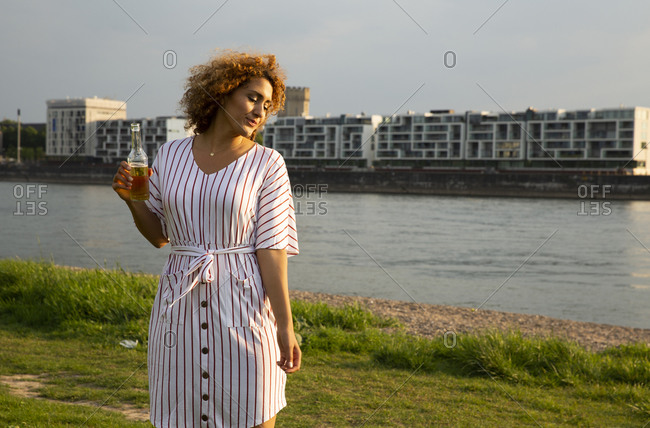 Mid adult woman holding beer bottle standing on grassy land against river in city at sunset