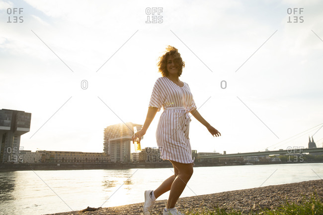 Carefree mid adult woman holding beer bottle dancing at riverbank against sky in city