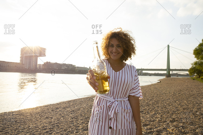Happy woman with curly hair holding beer bottle while standing on land against river in city