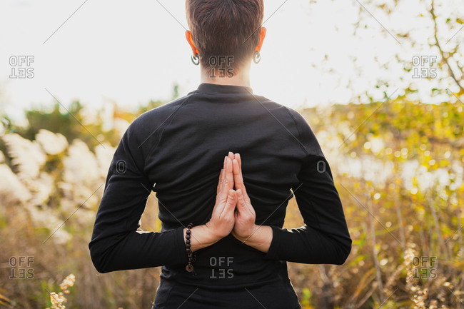 Woman practicing reverse prayer position while standing outdoors