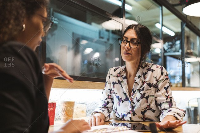 Confident young businesswoman looking at female professional while discussing during meeting at cafe