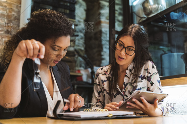 Businesswomen discussing over diary while planning at cafe