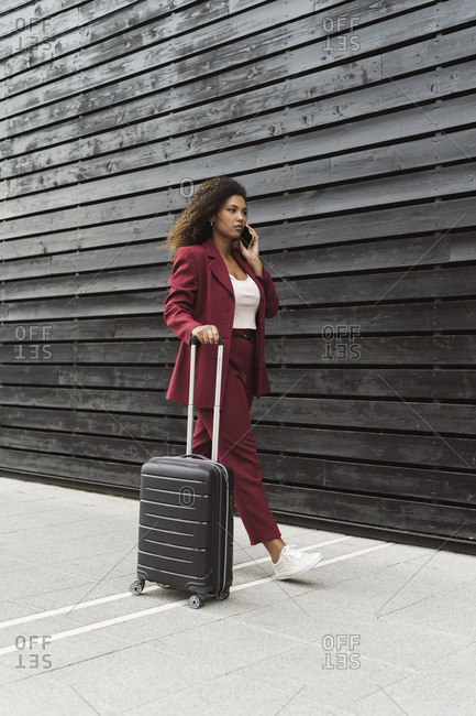 Young businesswoman talking on mobile phone while walking along wheeled luggage by wall on footpath