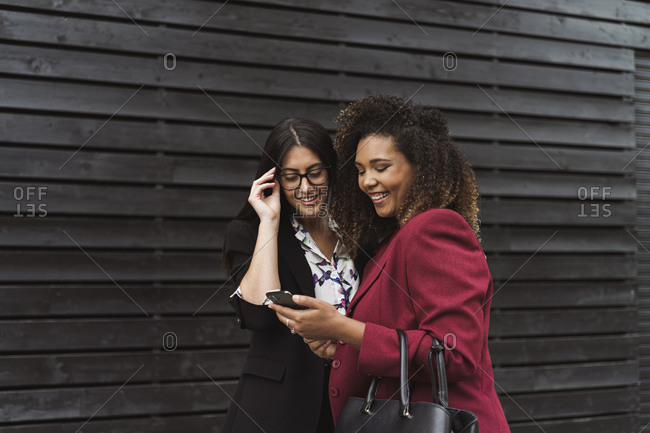 Happy female entrepreneur sharing smart phone while standing against black wall