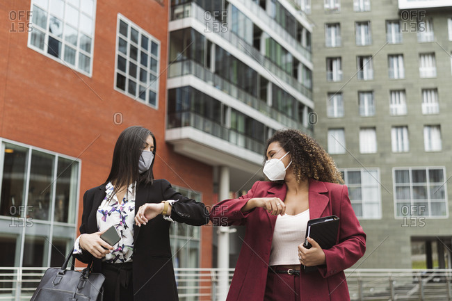 Young multi-ethnic female colleagues giving elbow bump against building in city
