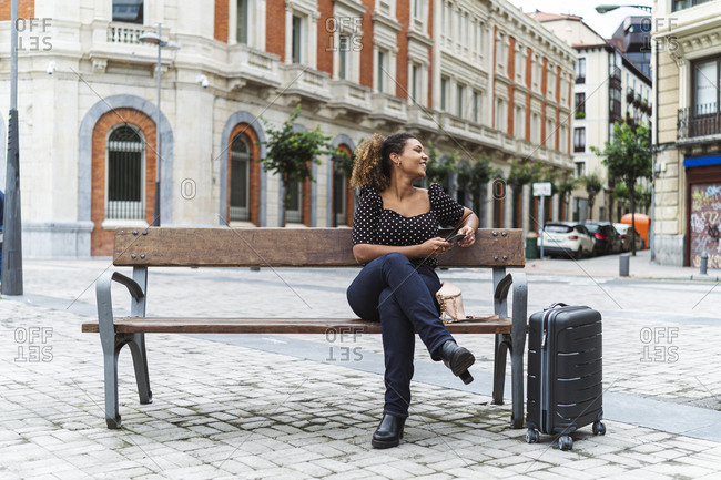 Smiling young businesswoman in smart casual sitting on bench by luggage