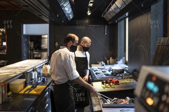Chefs wearing protective face masks preparing grilled vegetables in restaurant kitchen