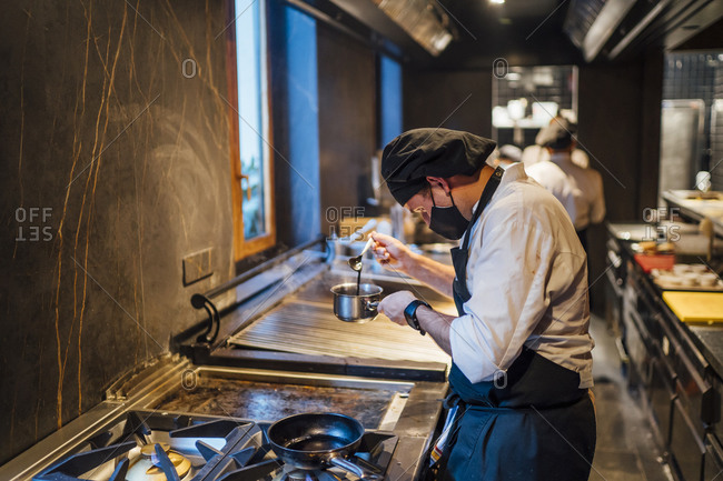 Chef wearing protective face mask preparing a sauce in restaurant kitchen