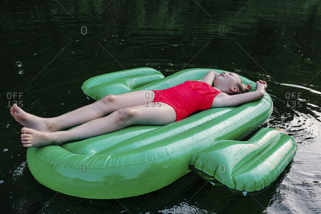 Girl wearing red swimwear relaxing on pool raft over river