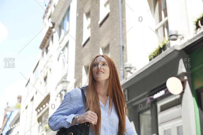 Beautiful redhead woman looking away against building in city