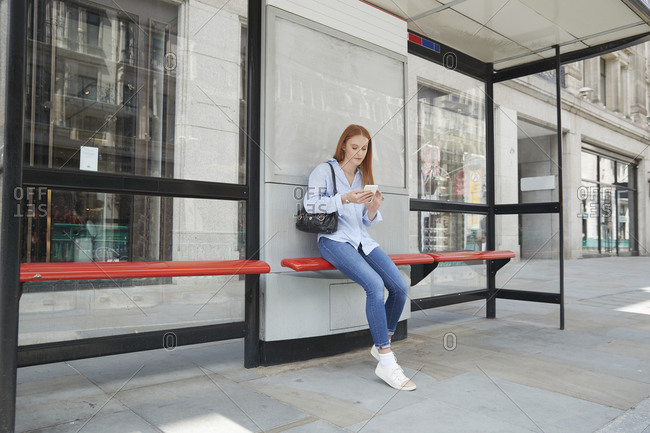 Young woman using smart phone while waiting at bus stop in city