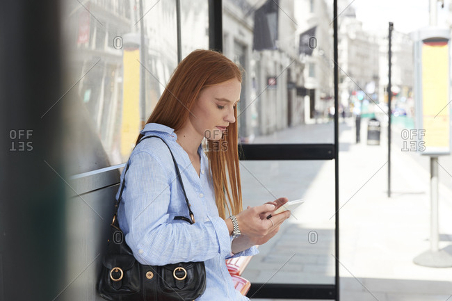 Beautiful redhead woman using mobile phone while waiting at bus stop in city