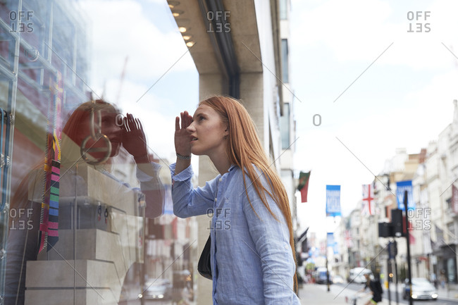Redhead woman shielding eyes while looking through store window in city