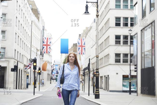Beautiful redhead woman walking on street in city