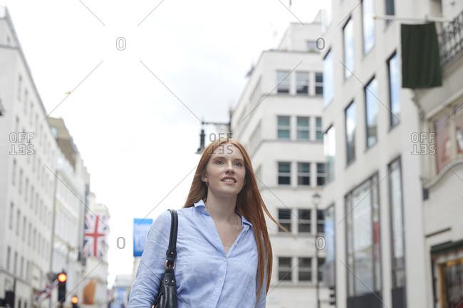 Redhead woman walking against buildings in city