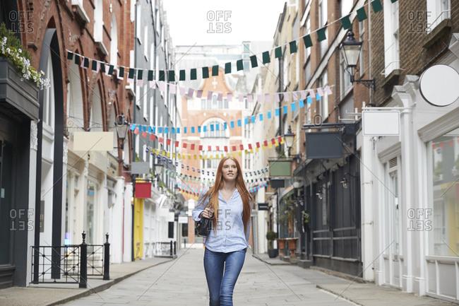 Beautiful redhead woman walking on alley against buntings amidst buildings in city