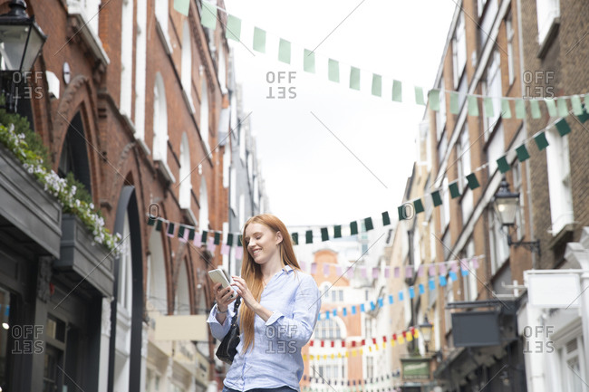 Smiling young redhead woman using smart phone while standing amidst buildings in city