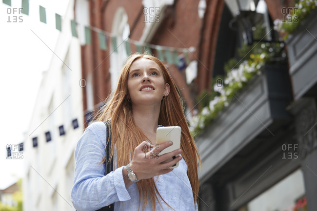 Smiling redhead woman looking away while walking with smart phone against building in city