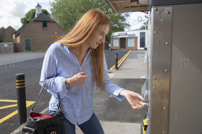 Young woman using ticket machine outside railroad station