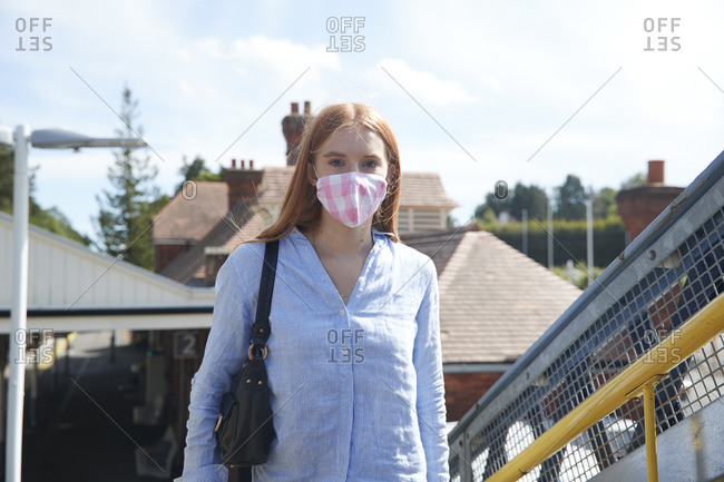 Young woman wearing protective face mask at railroad station