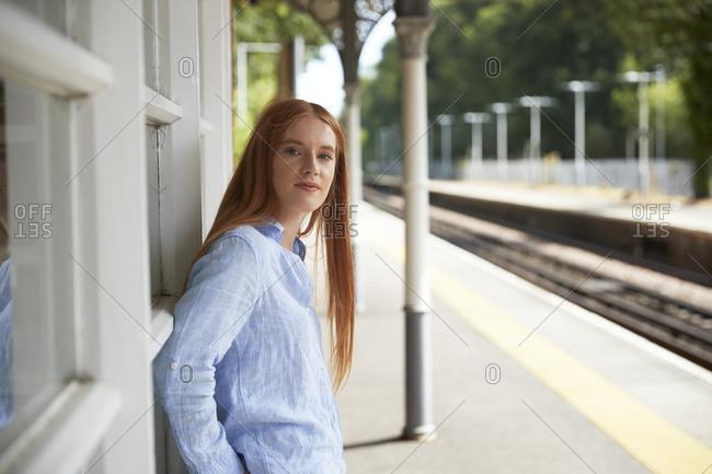 Beautiful woman standing at railroad station platform