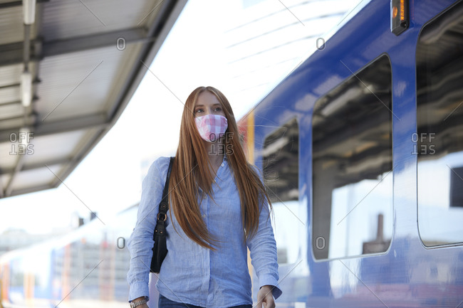 Young woman wearing protective face mask while walking at railroad station