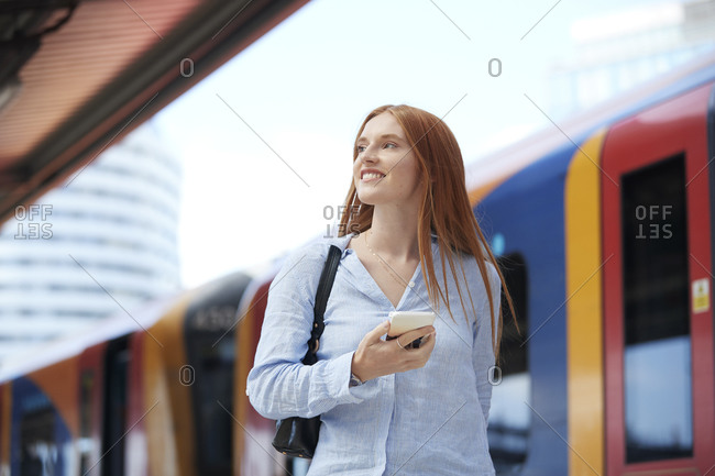 Young woman holding smart phone at railroad station