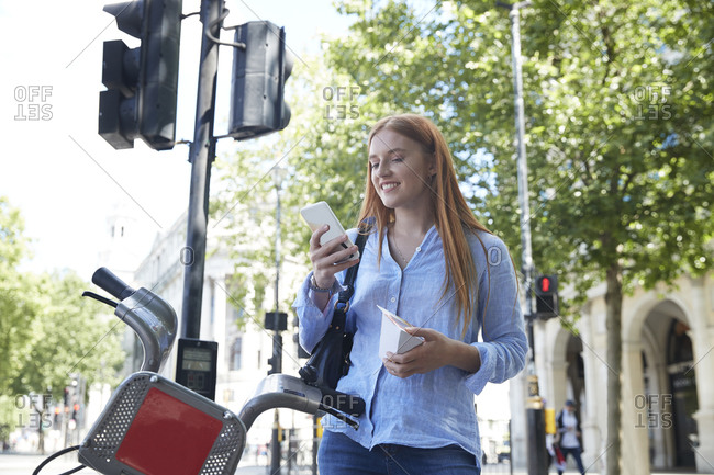 Happy young woman using smart phone while standing by hire bike in city