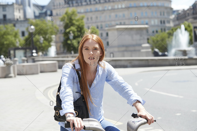 Beautiful woman riding hire bike on city street during sunny day