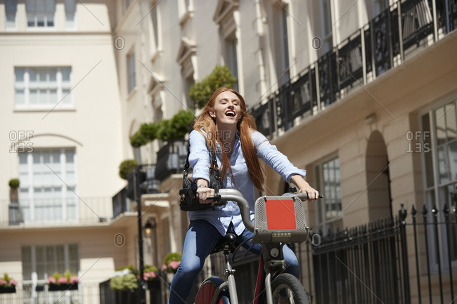 Cheerful woman riding hire bike in city during sunny day