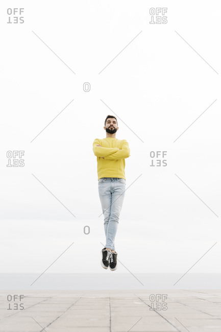 Carefree bearded young man with arms crossed jumping on footpath against white wall