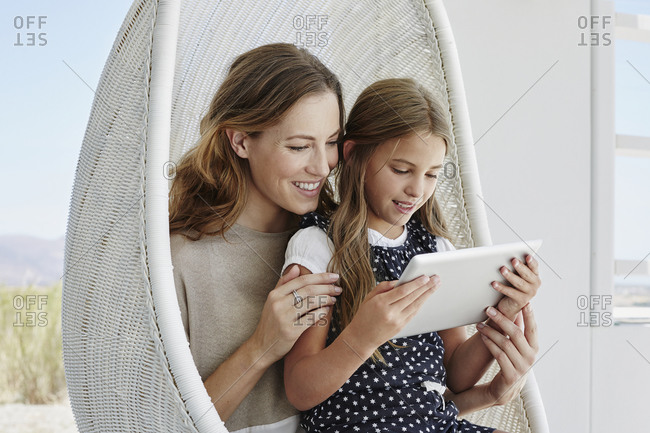 Smiling mother and daughter sitting in hanging chair using tablet together
