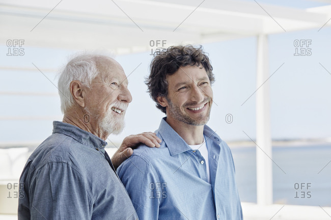 Portrait of confident senior man with adult son at a beach house