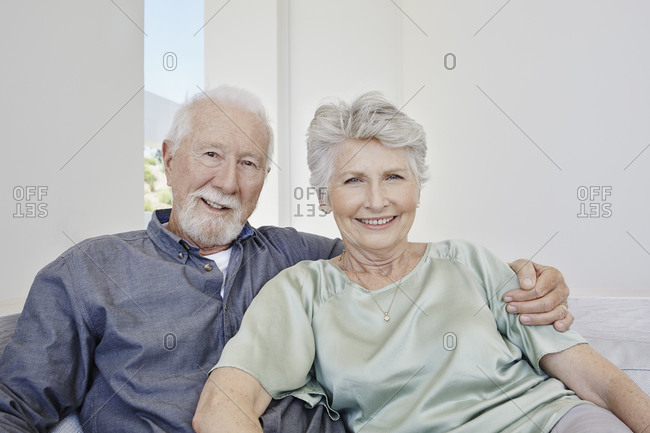 Portrait of smiling senior couple sitting on a couch in a villa