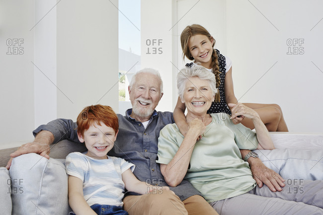 Portrait of happy grandparents with grandchildren on a couch in a villa