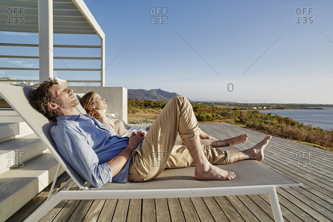 Couple lying on deck chairs at luxury beach house
