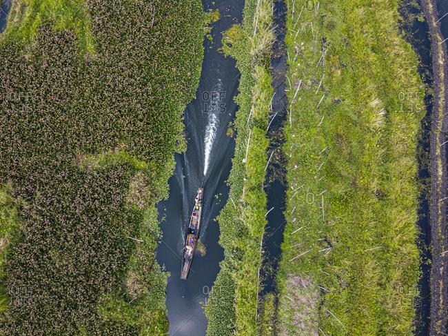 Myanmar- Shan State- Nyaungshwe Township- Aerial view of rowboat passing floating gardens on Inle Lake