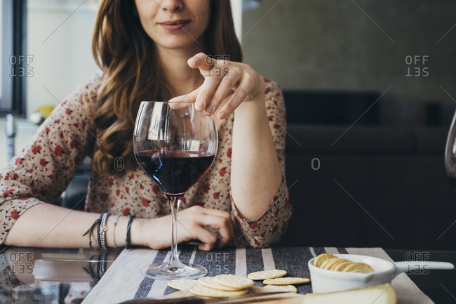 Young woman touching wineglass while sitting at dining table