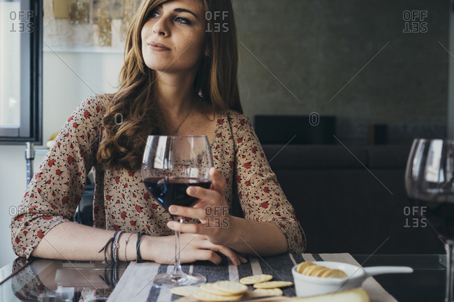 Beautiful young woman holding wineglass looking away while sitting at dining table