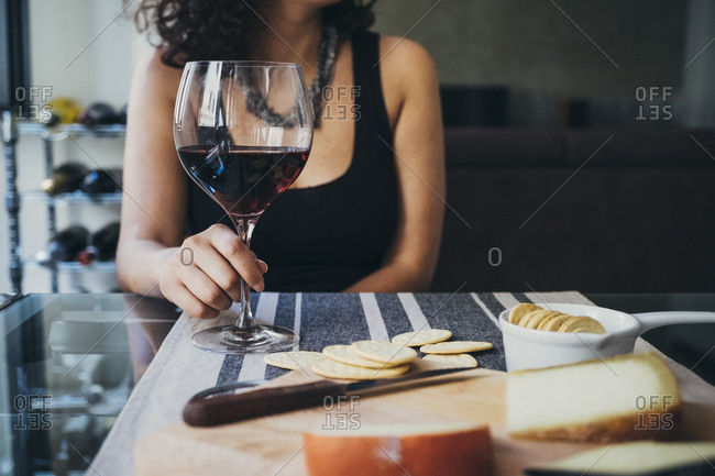 Young woman holding wineglass while sitting at dining table