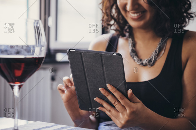 Smiling young woman using digital tablet while sitting at dining table