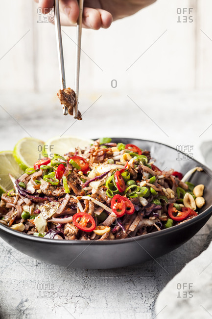 Fried rice noodles with vegetables- Pad Thai style with boys hand holding chopsticks