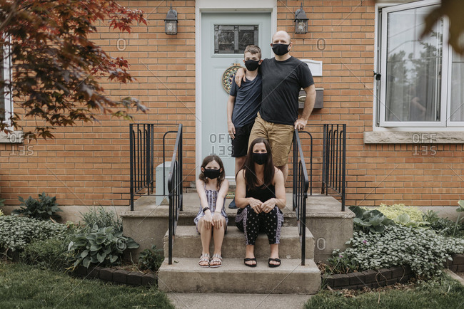 Family wearing masks against house in yard