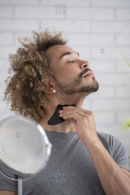 Close-up of young man massaging neck with gua sha stone at home