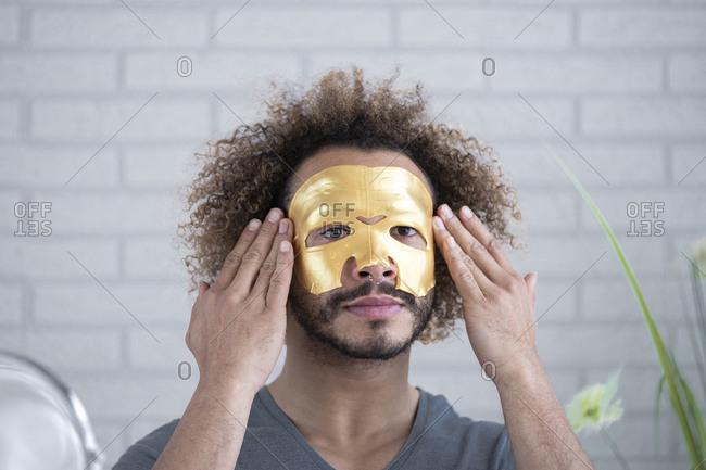 Close-up of young man applying facial mask at home