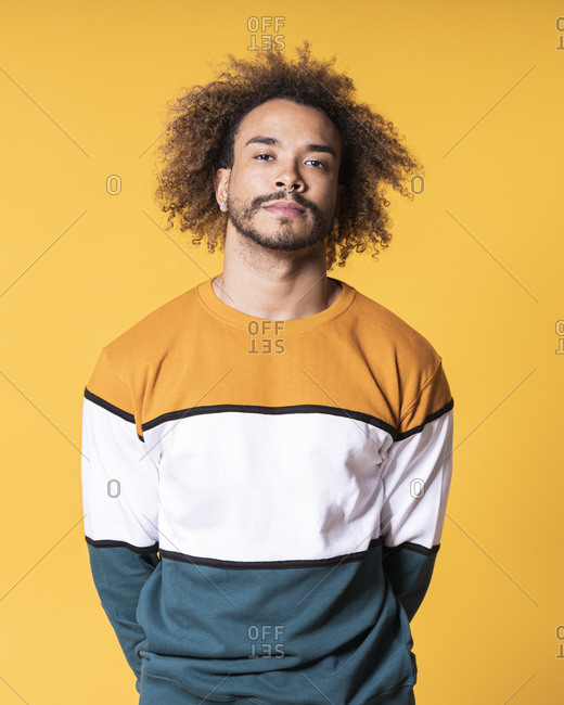 Handsome young man with curly hair standing against yellow background