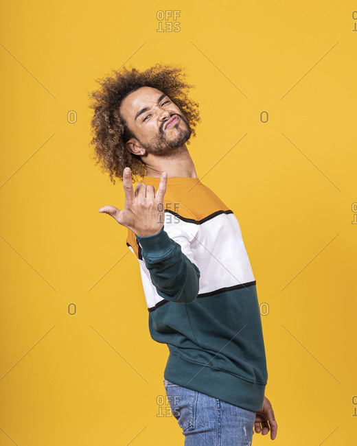 Cool young man with curly hair gesturing while standing against white background
